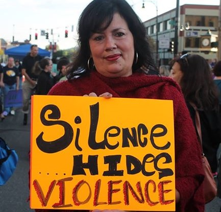 Walk a Mile walker with sign: silence hides violence